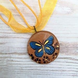Blue butterfly on terracotta clay pendant with yellow necklace